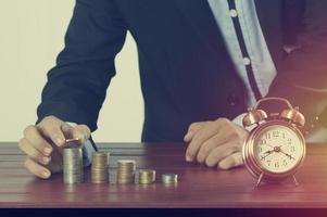 affärsman sätta pengar på hög med mynt med väckarklocka på arbetsbord koncept i tid till framgång foto
