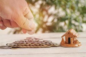 hand lägga pengar på staplade mynt och hus på trä bakgrund koncept i tillväxt sälja köpa spara och investera i affärer hemma foto
