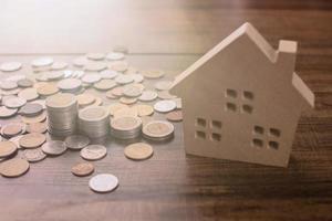 fastigheter och köpa hus koncept staplade med massor mynt på trä bord med modell hus spara pengar för att betala för investering fastigheter och bostäder foto