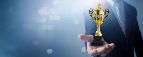 mästare och framgång vinnare koncept affärsman som håller kopp ledarskapstrofé och mästare av affärer på mjukblå och bokeh bakgrund foto