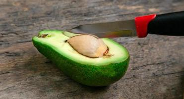 färskt avokadosnitt på hälften på träskiva med knivbakgrund foto
