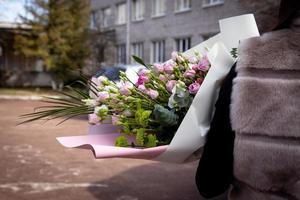 bakifrån av en flicka i en pälsväst som står på gatan som håller en bukett blommor foto