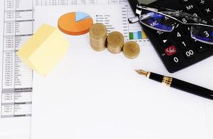 inteckning lån koncept med gult papper närbild funtain penna och mynt och miniräknare och glasögon foto
