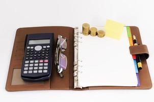 affärsidé med pengar mynt stack och gult papper hus och miniräknare och glasögon och reservoarpenna på affärsbokbok på vit bakgrund foto