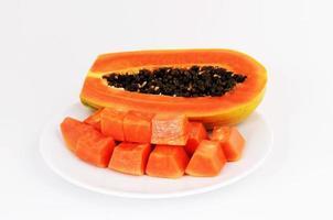 läckra papayafrukter på maträtt som isoleras på vit bakgrund foto