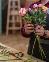 blomsterhandlare man gör blombukett i affären foto