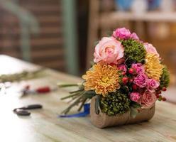 vacker blombukett i bordet med bukett blomsterhandlare utrustning foto