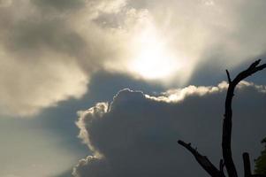 vacker soluppgång starkt solljus kom genom svarta dramatiska moln foto