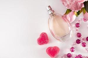 flaska parfymblommor och hjärtan på en ljus bakgrund foto