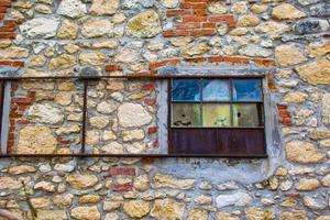 färgglatt fönster i en gammal ladugård på en vägg foto