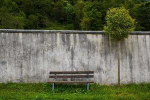 tom bänk med en gammal vägg foto