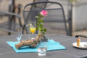 efter festen blommar dekoration med begagnade glas och tallrikar på ett uteplatsbord foto