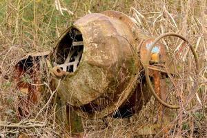 gammal rostig cementblandare står bevuxen i en lövlös tornhäck foto