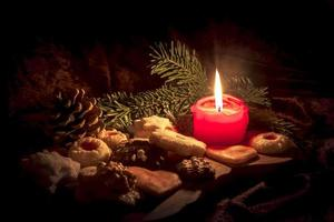 brinnande rött ljus står mellan dekorerade julkakor på en träskiva foto