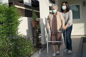 asiatisk senior eller äldre gammal damkvinna går med rullator och bär en ansiktsmask för att skydda säkerhetsinfektion covid 19 coronavirus foto