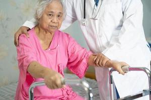 asiatisk sjuksköterska sjukgymnast läkare hjälp asiatisk äldre kvinna patient med rullator foto