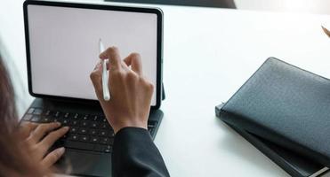 affärskvinna som arbetar med en penna på en digital minnestavla med en bärbar dator i ett modernt kontor foto