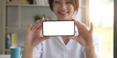 mockupbild av en vacker kvinna håller en mobiltelefon med tom vit skärm foto