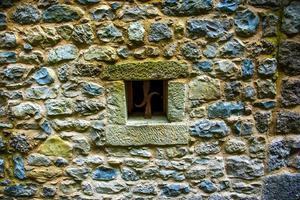 litet fyrkantigt fönster på stenväggen foto