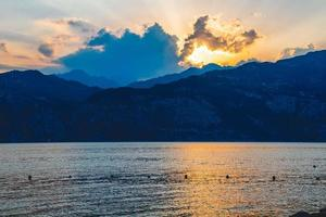 ljus och skuggor från solnedgången över Gardasjön foto