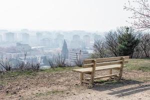 Tom träbänk i våren parkerar över staden foto