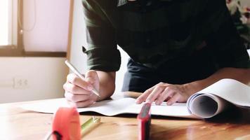 bild av ingenjör som ritar en blåtrycksdesignbyggnad eller hushållsingenjörs arbetsplats med ritningar blyertsgrad och skyddshjälmindustrikoncept foto
