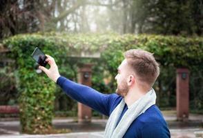 ung man med ryggen mot kameran tar en bild med sin mobiltelefon foto