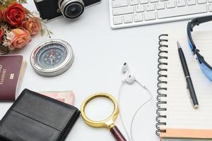 datortangentbord med kamera och anteckningsbok på vit bakgrund foto