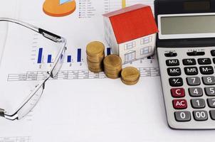bostadslån koncept med närbild mynt stack och papper hus och miniräknare och glasögon foto