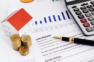 bostadslån koncept med närbild reservoarpenna och låneformulär och mynt stack och papper hus och beräkna foto