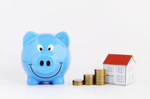 pengar sparande plan koncept med blå spargris och mynt stack och papper hus isolerad på vit bakgrund foto