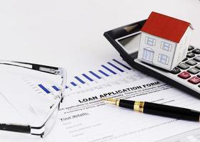 närbild av reservoarpenna och låneansökningsformulär och pappershus på miniräknare och glasögon för bostadslån koncept foto