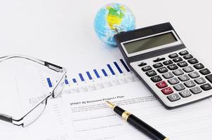 affärsidé med närbild reservoarpenna och miniräknare och glasögon på finansiell rapport foto