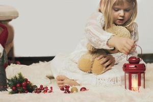 liten flicka som sitter på mattan med sin nallebjörn som leker med juldekoration foto