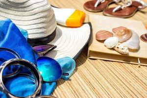 stråhatt, sarong, solglasögon och flip flops på en strand foto