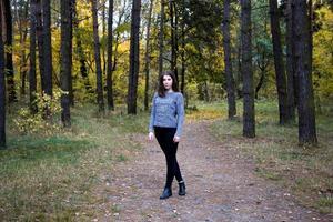 söt flicka i en grå tröja med hängslen på tänderna som står på vägen i höstskogen foto