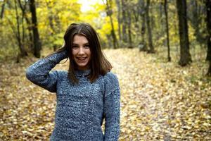 söt flicka i en grå tröja i höstskogen foto