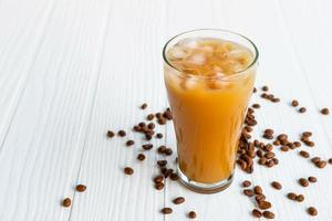 iskaffe i ett glas på en vit träbakgrund foto