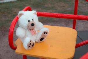 närbild av en nallebjörn som sitter på en barns gunga foto