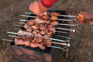man steker shish kebab på grillen foto