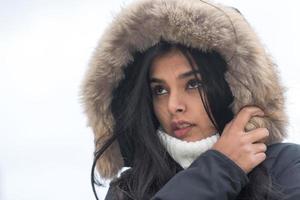 ung kvinna vinter porträtt söt ung kvinna fryser i vinterrock står på gatan foto