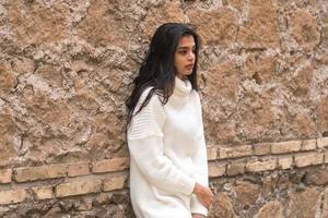 ung kontemplativ brunettkvinna som lutar sig mot en tegelvägg foto