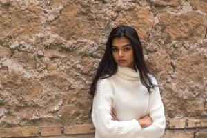 porträtt av en ung romantisk brunettkvinna som lutar sig mot en tegelvägg med korsade armar foto