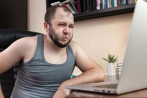 ung skäggig kille avslappnad med bärbar dator foto
