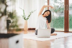 asiatisk kvinnakondition hemma gör stretching foto