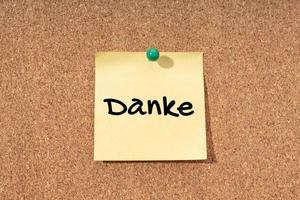 danke - tackord på tyska på gul anteckning på korkbrädet foto