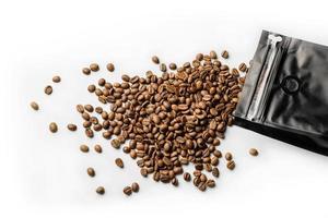 bönor kaffe som spillts från en svart påse på en vit yta foto