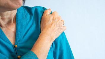 äldre kvinna som får axelsmärta från frusen axel foto
