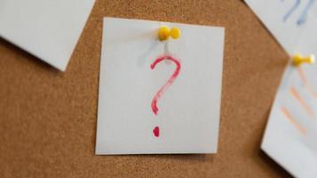 rött frågetecken på ett papper och många papper foto