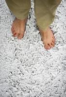 bara fötter på snöigt gräs foto